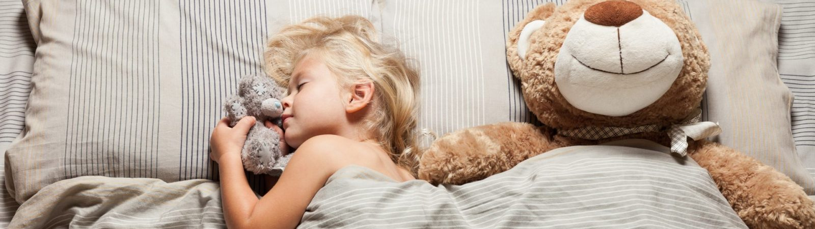 Beautiful child girl sleep in bed with teddy bear. Little caucasian kid. Rest cute dream.